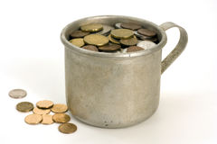 Old aluminum mug and coins. Royalty Free Stock Photography