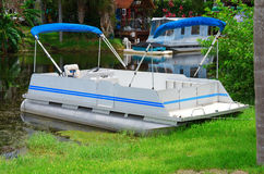 Old aluminum pontoon boat pulled up on shore Royalty Free Stock Images
