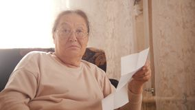 An old amazed woman in glasses sitting in the armchair, holding an utility bills and looking in the camera stock photography