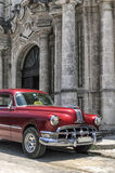 Old american car in Old Havana, Cuba. Red vintage taxi in front of a church facade in Old Havana, Cuba stock photo
