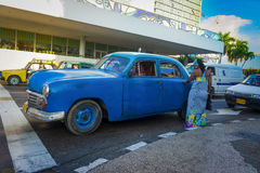 Old american car picking up a passenger in Havana Royalty Free Stock Image