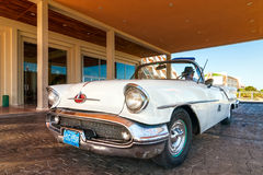 Old american car standing near hotel entrance Royalty Free Stock Images