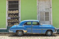 Old american car in Trinidad, Cuba. A blue classic car parked in front of a typical colonial house, Trinidad, Cuba royalty free stock photos