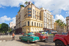 Old american cars near a modern hotel in Havana. Old american cars near a modern hotel December 2,2013 in Havana,Cuba.Thousands of these cars,bought before1959 Stock Image