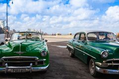 Old american cars on the road in Havana Malecon, Cuba. Havana,Cuba - January 22,2017: Old american cars on the road in Havana Malecon. The Malecon officially Royalty Free Stock Image