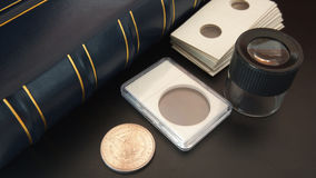 Old American silver dollar on black table with magnifying glass, numismatic supplies and album for coins. Numismatic scene Stock Photography