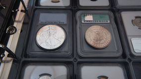 Old American silver dollar and new American silver dollar on album for coins collection Royalty Free Stock Photo