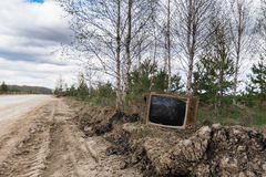 Old analog discarded television set in the forest Stock Photos