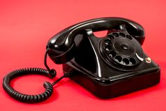 Old black phone isolated on a red background Stock Photography