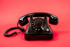 Retro black phone isolated on a red background. Old analog rotary dial black phone isolated on red background. Retro communications technology concept Stock Image
