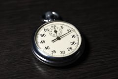 Old analog stopwatch lies on on a dark wooden surface, close-up stock photography