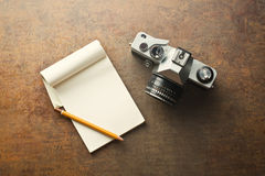 Old analogue camera and notepad. The old analogue camera and notepad Royalty Free Stock Images