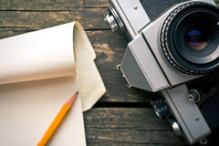 Old analogue camera and notepad Royalty Free Stock Photography