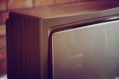 Old analogue TV. Old and dusty analogue tube TV close up on a brick wall background stock photos
