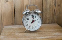 Old analoque bed site clock. An old fashioned silver coloured bed side analogue pre digital alarm clock Stock Photography