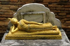 Old anceint Sleeping Buddha statue On the old brick wall is the. Background Stock Photos
