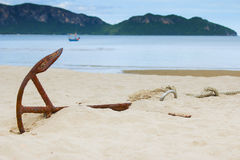 Old Anchor on the beach with mountains and sea background as hor Royalty Free Stock Photography