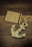 Old anchor with cork cover book on wooden background Royalty Free Stock Photo