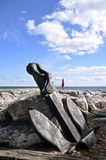 Old anchor propped up on large rocks Stock Images