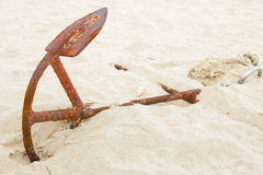 Old Anchor on sand of the beach Stock Photo