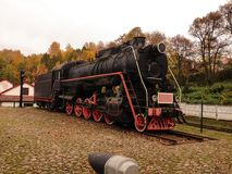 Old school ancient train. Old ancient black iron train standing on the rails with fall background Royalty Free Stock Photography
