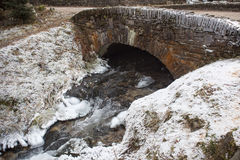 Old ancient bridge over a stream. Stock Image