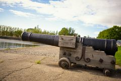 Old ancient cannon gun aims across the harbour on house Stock Photo
