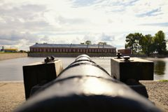 Old ancient cannon gun aims across the harbour on house Royalty Free Stock Images