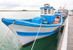 Old ancient fishing boat near the pier. Stock Images