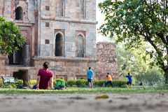 Old ancient Indian stone building in the park with people working out. Old ancient Indian stone building in the park New Delhi early morning with people working Royalty Free Stock Photos