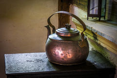 The old and ancient kettle on a stove Royalty Free Stock Photo