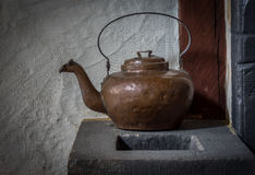 The old and ancient kettle on a stove Stock Image