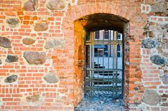 An old ancient metal door with a sturdy prison bars on a thick, wide wall of red clay scratched cracked brick stock images