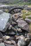 Old ancient packhorse bridge over mountain stream in Autumn Royalty Free Stock Images