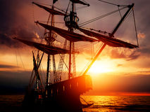 Old ancient pirate ship on peaceful ocean at sunset. royalty free stock image