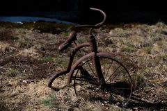 Old ancient rusty tricycle with grass background stock images