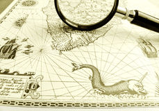 Old Ancient sea chart, magnifier. Exotic tourism and travels theme image. - An antique sea sailing chart taken with a magnifying glass placed on it.  With ornate Stock Photography