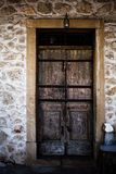 An old ancient wooden door in stones background in Corfu Greece. Antique castle entrance in rocks wall and frame made of wood. Bea. Old ancient wooden door in stock photography