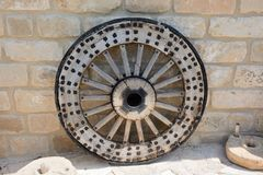 Old, ancient wooden wheel with a metal rim, against the background of a stone wall royalty free stock photo