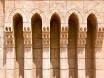 An old ancient yellow stone strong wall with arches in patterns and columns in an Arab Muslim Islamic warm tropical country in the. Texture of the old ancient royalty free stock image