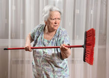 Old angry woman threatening with a broom Royalty Free Stock Photography