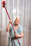 Old angry woman threatening with a broom Stock Photos