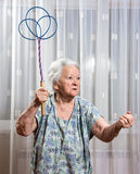 Old angry woman threatening with a carpet beater. At home Stock Image