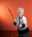 Old angry woman threatening with a rolling pin Royalty Free Stock Photos