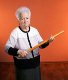 Old angry woman threatening with a rolling pin Stock Photo