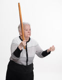 Old angry woman threatening with a rolling pin Stock Image