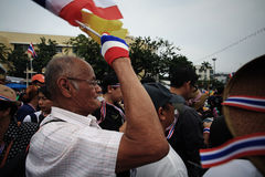 Old anti-government man blows whistle and raise Thai flag Royalty Free Stock Photography