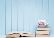 Old antiquarian books, glasses and china cup on the bookshelf Stock Photography