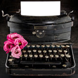 Old antique black vintage typewriter. And empty paper for copy space, with red romantic flowers Royalty Free Stock Photos