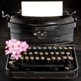 Old antique black vintage typewriter with flowers. Old antique black vintage typewriter and empty paper for copy space, with pink romantic cherry blossom flowers Stock Image
